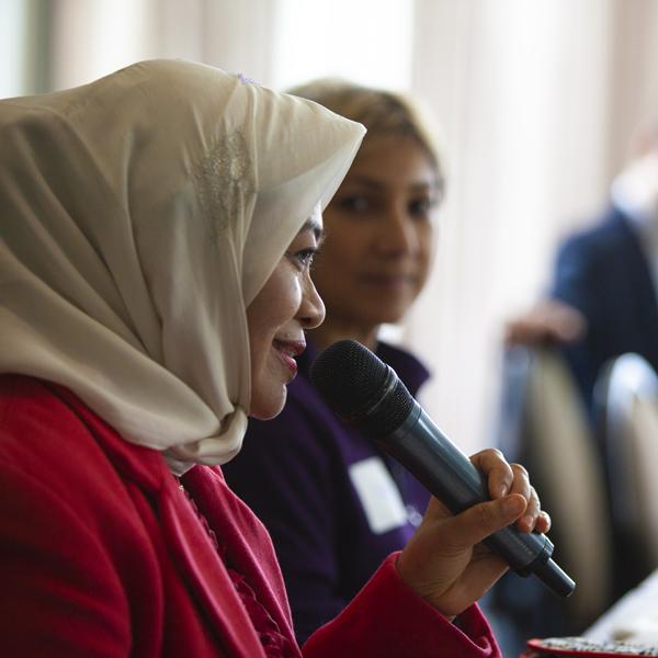 Representative in head scarf speaks into microphone
