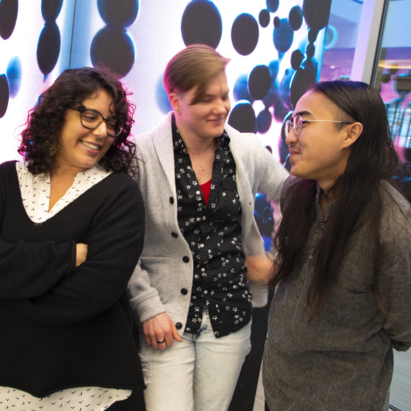 Three participants chat and smile at Creating Change
